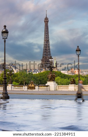 Seen from the Alexander iii Bridge. early morning view on eiffel tower with beautiful clouds and colors in sky, and business man walking out of the image - stock photo