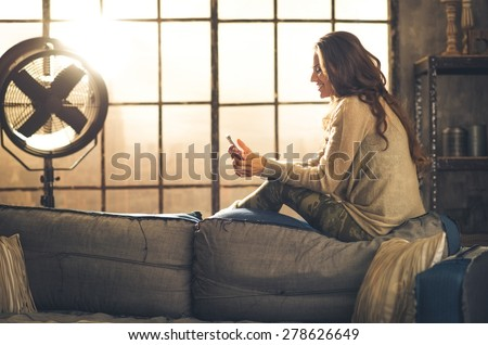 Seen from the side,a brunette woman is smiling, looking down at her phone sitting on the back of a sofa. Industrial chic ambiance and cozy atmosphere, sunlight is streaming through the loft window. - stock photo