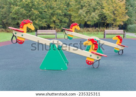 Seesaw in the shape of the horses for the playground. Small depth of field - stock photo