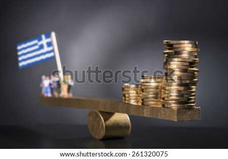 Seesaw with coins on one side and a group of people with the Greek flag on the other side. - stock photo