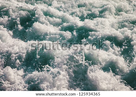 Seething sea surface covered with white foam - stock photo