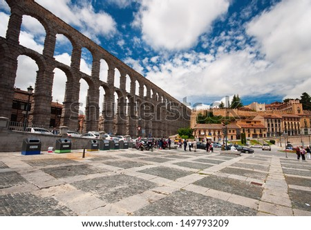 SEGOVIA, SPAIN - 14 JUNE 2010: Aqueduct of Segovia on 14 June 2010. The Aqueduct of Segovia is a Roman aqueduct and one of the most significant and best-preserved ancient monuments left in Spain.  - stock photo