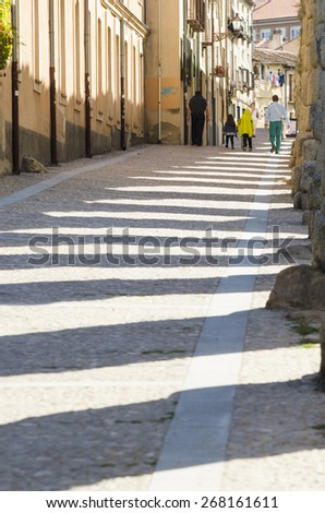 SEGOVIA, SPAIN - SEPTEMBER 20, 2014: A group of people walking near the Roman aqueduct in the city, heritage of humanity. - stock photo