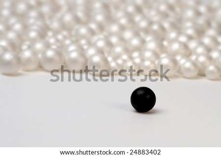 Segregation concept shot with a single black ball and group of white ones - stock photo