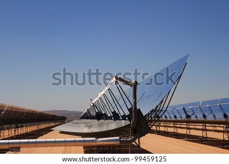 SEGS solar thermal energy desert electricity plant with parabolic mirrors concentrating the sunlight with blue sky copy space - stock photo