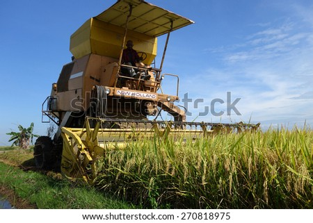 SEKINCHAN, MALAYSIA- NOV 12; Worker uses machine to harvest rice on paddy field in Sekinchan, Malaysia on November 12, 2014. Sekinchan is one of the major rice supplier in Malaysia. - stock photo