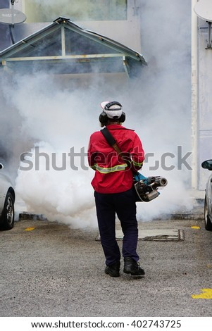 SELANGOR, MALAYSIA - APRIL 7 2016 : Worker fogging residential area with insecticides to kill aedes mosquito breeding ground, carrier of dengue virus