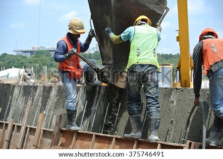 SELANGOR, MALAYSIA - AUGUST 2014: Construction workers casting concrete wall on August 18, 2014 at Cyberjaya, Selangor, Malaysia. The concrete was lifted using basket by mobile crane.