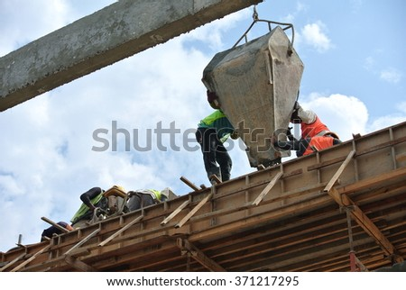 SELANGOR, MALAYSIA AUGUST 07, 2014: Group of construction workers casting beam at Selangor, Malaysia. The concrete was lifted using basket by mobile crane.