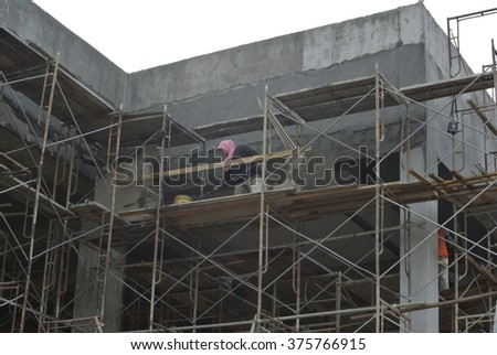 SELANGOR, MALAYSIA â?? AUGUST 2014: Plastering work by construction workers at high level using scaffolding as the platform.