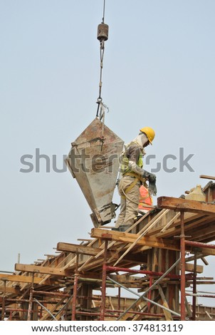 SELANGOR, MALAYSIA - JULY, 2014: Group of construction workers casting beam on August 06, 2014 at Sepang, Selangor, Malaysia. The concrete was lifted using basket from mobile crane.