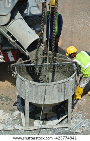 SELANGOR, MALAYSIA -MARCH 07, 2016: Concrete mixer lorry pouring liquid concrete into and the tower crane bucket at the construction site.   - stock photo