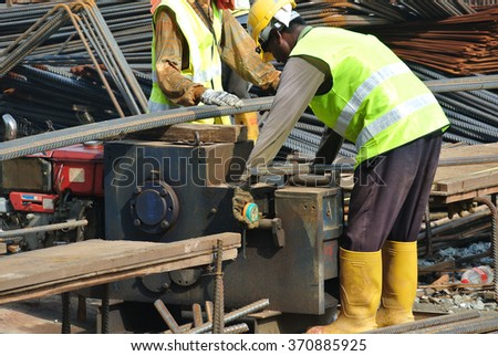 SELANGOR, MALAYSIA â?? MARCH 17, 2015: Construction workers working at the bar bending yard in the construction site.