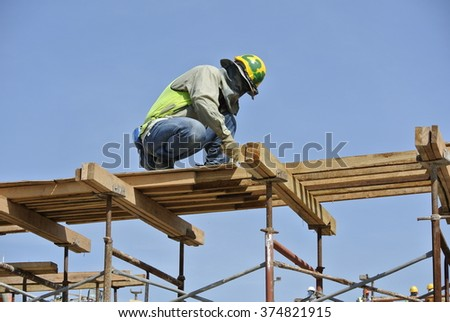 SELANGOR, MALAYSIA � MAY 2014: A construction workers installing beam formwork. Formwork is located at the high level that requires the workers to use scaffolding.