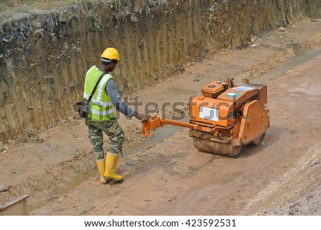 SELANGOR, MALAYSIA -NOVEMBER 25, 2015: Construction workers using baby roller compactor to compact soil at the construction site.