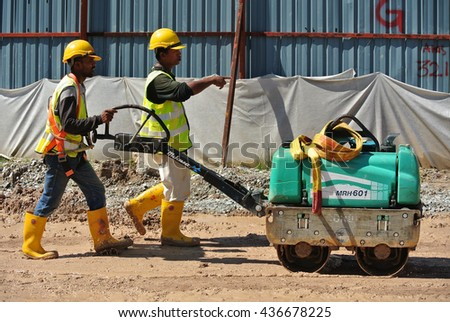 SELANGOR, MALAYSIA -NOVEMBER 25, 2015: Construction workers using baby roller compactor to compact soil at the construction site. - stock photo