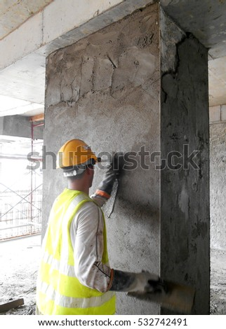 SELANGOR, MALAYSIA -OCTOBER 15, 2016: Construction worker plastering wall using cement plaster at the construction site in Selangor, Malaysia