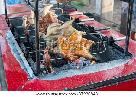Select focus at front chicken in Row of Grilled chicken in the local street food market. Rotating machine are grilled whole chicken. - stock photo