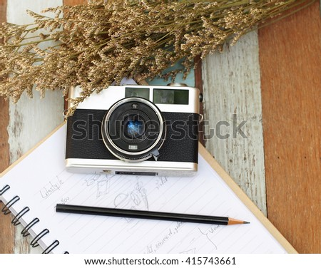 Select focus vintage old camera on the book and with a pencil, flower on the wooden. - stock photo
