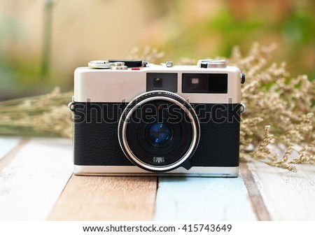 Select focus vintage old camera with flower on the wooden.  - stock photo