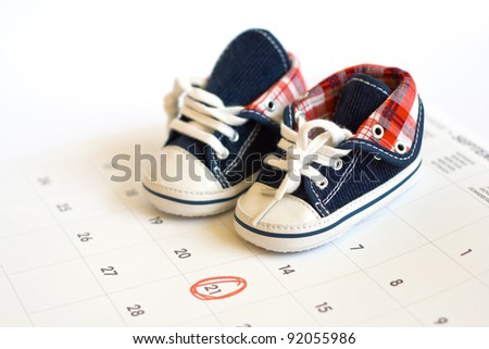 Selected due date in the calendar and detail of baby shoes - stock photo