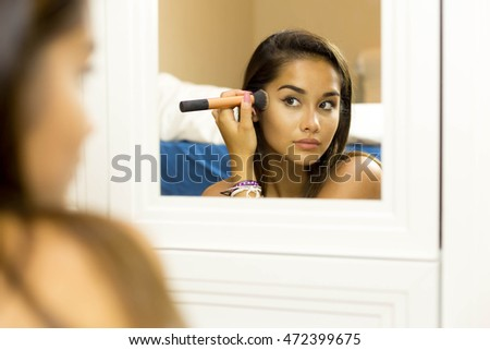 Selected focus on hand Reflective mixed race young woman applying her make up on looking in the mirror