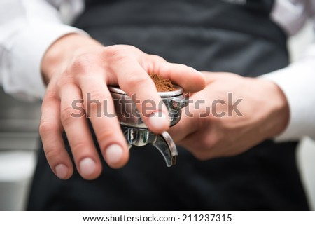 Selected focus on the hands of professional barista pressing coffee with his hand wearing the black uniform on background - stock photo