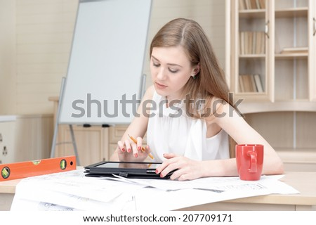 Selected focus on young fair-haired architect sitting at the table with different schemes diagrams and plans on it working on the tablet. White board for copy place on background
