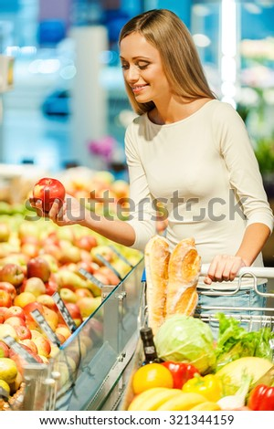 Selecting freshness and quality. Beautiful young woman holding apple and smiling while standing in a food store