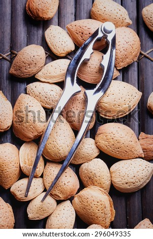 Selection of almonds in the vintage bamboo wooden tray with a nut cracker on the top, top view - stock photo
