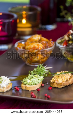 Selection of Appetizers on Square Plate on Set Table with Cutlery, Candles, and Potted Plant