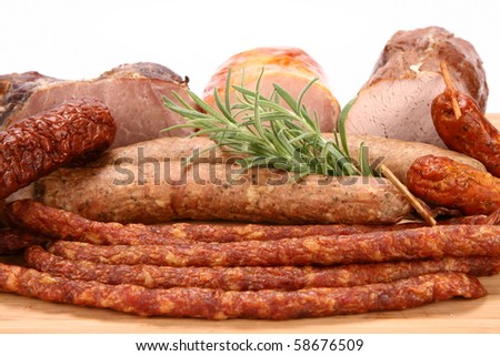 Selection of cold meat (ham, sirloin, headcheese, sausages, hot dogs) decorated with rosemary - stock photo