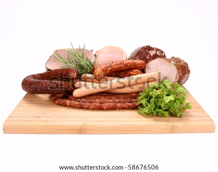 Selection of cold meat (ham, sirloin, headcheese, sausages, hot dogs) on a chopping board decorated with rosemary and parsley - stock photo