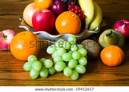 Selection of colorful, fresh, natural looking fruit in an old bowl placed on wood.