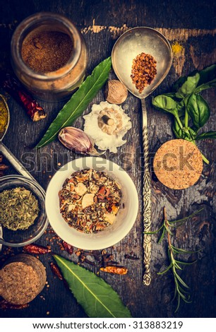 selection of colorful herbs and spices in spoon and bowl on rustic wooden background, top view, toned