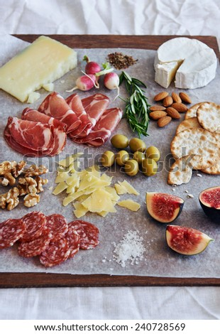 Selection of cured meat charcuterie salami, coppa, with brie camembert gruyere cheese served with olives nuts crackers and fruit - stock photo