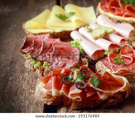 Selection of delicious open sandwiches topped with gouda cheese and assorted meats including roast beef, mortadella, ham and salami - stock photo