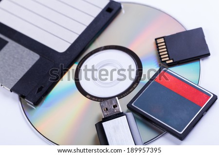 Selection of different computer storage devices for data and information including a CD-DVD, floppy disc, USB key, compact flash card and SD card viewed in a neat arrangement from overhead - stock photo