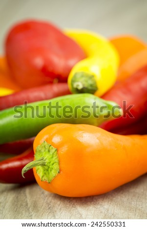 Selection of different varieties of colorful capsicum peppers with sweet bell peppers, chili pepper and cayenne used to produce paprika spice and as an ingredient in cooking, on a wooden table - stock photo