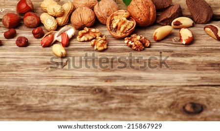 Selection of festive fresh nuts both shelled and in their shells on rustic wood with copyspace including almonds, hazelnuts, brazil nuts, peanuts and walnuts - stock photo