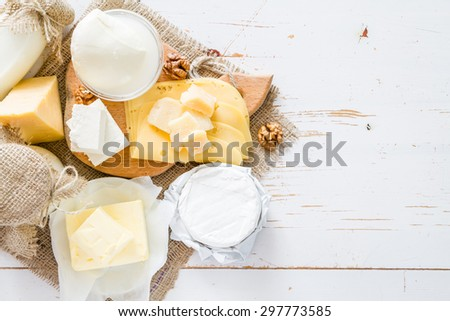 Selection of fresh dairy products - cheese, yogurt, butter, white wood background - stock photo