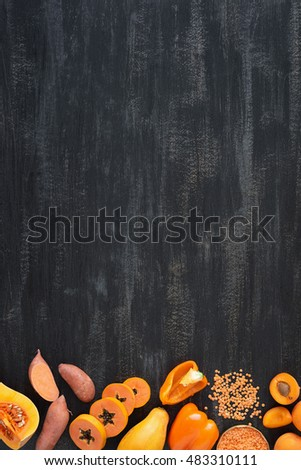 selection of fresh orange vegetables on dark rustic distressed background, part of a set