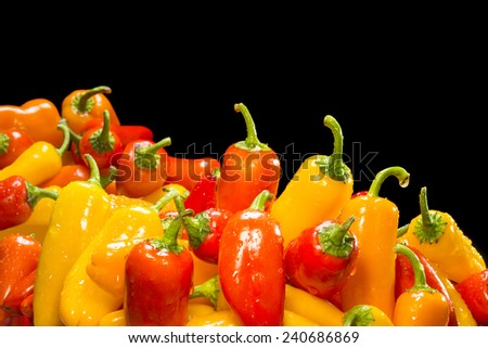 Selection of fresh, ripe red, yellow and orange peppers framed against a black background for placement of copy. - stock photo