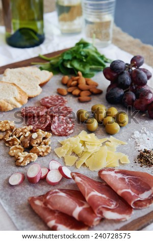 Selection of gourmet cured meat charcuterie salami, coppa capicola, with brie camembert gruyere cheese served with olives nuts fruit and wine - stock photo