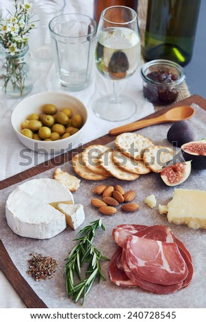 Selection of gourmet cured meat charcuterie salami, coppa, with brie camembert gruyere cheese served with olives nuts and fruit - stock photo