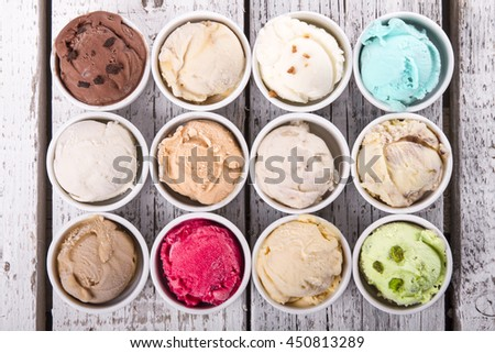 Selection of gourmet flavours of Italian ice cream in vibrant colors served in individual porcelain cups on an old rustic wooden table in an ice cream parlor, angle view - stock photo