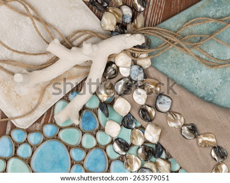 selection of materials in a nautical theme with a blue ceramic mosaic-like sea pebbles, a linen cloth, pearl beads, salted wood, twine and coral - stock photo