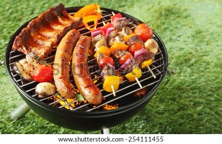 Selection of meat grilling over the coals on a portable barbecue with spicy sausages, beef kebabs and racks of ribs, outdoors on green grass with copyspace - stock photo