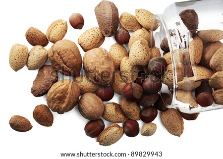 Selection of nuts in a glass jar on white background - stock photo