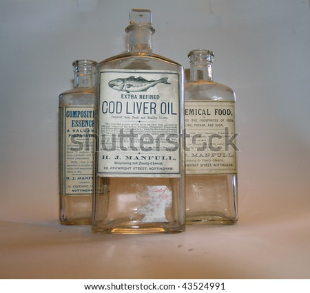 selection of old medicine bottles on plain background with soft lighting - stock photo